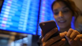 Menina nova do turista da raça misturada que usa o telefone celular perto da placa da partida no aeroporto 4K Banguecoque, Tailân video estoque