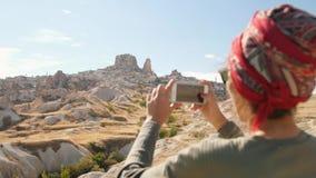 A menina nova do turista da raça misturada toma fotos do vale do deserto usando o telefone celular Cappadocia, Turquia 4K filme