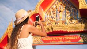 Menina nova do turista do moderno da raça misturada que toma a foto com telefone celular da porta tailandesa da entrada do templo vídeos de arquivo