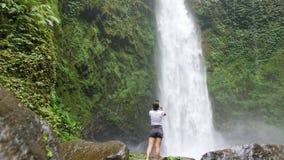 A menina nova do viajante toma fotos usando o telefone celular de cachoeira surpreendente da selva em Bali, Indonésia 4K, cinemát video estoque