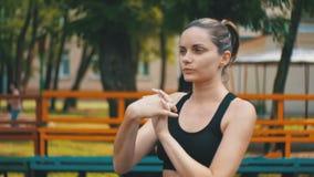 A menina nova dos esportes atléticos executa um aquecimento das mãos no campo de esportes no parque vídeos de arquivo