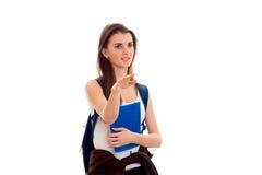 Menina nova dos estudantes de Cutie com a trouxa azul no ombro e dobradores para os cadernos no levantamento das mãos isolados no Fotografia de Stock Royalty Free