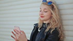 Menina nova e bonita elegante com um smartphone nas mãos A menina está olhando a tela do telefone Contra a video estoque