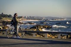 A menina nova e bonita está montando uma bicicleta pelo cais ao lado do Oceano Atlântico fotos de stock royalty free