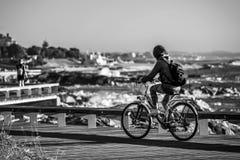 A menina nova e bonita está montando uma bicicleta pelo cais ao lado do Oceano Atlântico imagens de stock royalty free