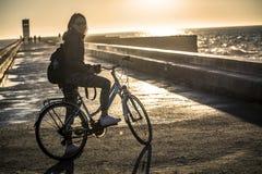 A menina nova e bonita está montando uma bicicleta pelo cais ao lado do Oceano Atlântico foto de stock royalty free