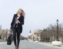 Menina nova e bonita que anda ao longo da rua principal da cidade imagem de stock