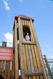 Menina nova e feliz na torre do campo de jogos. Imagem de Stock