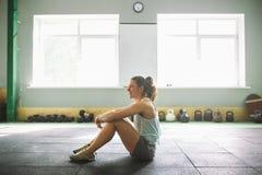Menina nova e forte com um sorriso que faz exercícios para os músculos do estômago, imprensa no assoalho no esporo imagens de stock royalty free