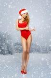 Menina nova e 'sexy' de Santa em um roupa de banho vermelho em um fundo nevado Fotos de Stock