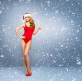 Menina nova e 'sexy' de Santa em um roupa de banho vermelho em um fundo nevado Fotografia de Stock
