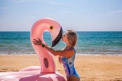 A menina nova e 'sexy' em um roupa de banho azul beija o flamingo cor-de-rosa inflável em um roupa de banho azul imagem de stock