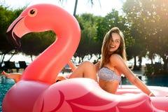 Menina nova e 'sexy' que tem o divertimento e que ri em um colchão cor-de-rosa gigante inflável do flutuador da associação do fla fotografia de stock royalty free