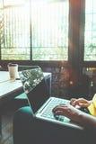 A menina nova encantador do moderno entrega o trabalho em seu portátil que senta-se na tabela de madeira em uma cafetaria Foto de Stock