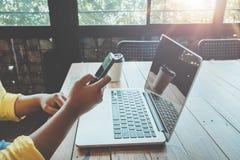 A menina nova encantador do moderno entrega usando-se em seu telefone esperto que senta-se na tabela de madeira em uma cafetaria Imagem de Stock