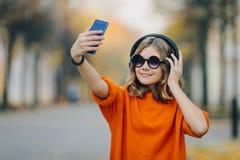 A menina nova feliz do moderno na rua toma uma foto em um smartphone Louro bonito com fones de ouvido e smartphone imagem de stock royalty free