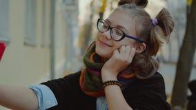 A menina nova feliz do moderno na rua toma uma foto em um smartphone Louro bonito com smartphone para fazer um selfie video estoque