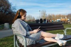 A menina nova, feliz do ruivo na primavera no parque perto do rio escuta a música através dos fones de ouvido sem fio do bluetoot fotografia de stock