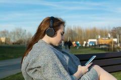 A menina nova, feliz do ruivo na primavera no parque perto do rio escuta a música através dos fones de ouvido sem fio do bluetoot fotos de stock royalty free