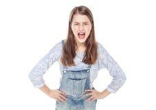 Menina nova irritada da forma em gritar dos macacões das calças de brim isolado foto de stock royalty free