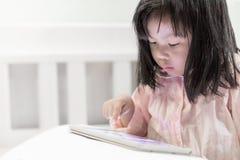 Menina nova nos pyjamas que jogam a tabuleta na cama foto de stock royalty free