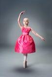 Menina nova pequena da bailarina no vestido cor-de-rosa que faz a separação ginástica Fotografia de Stock