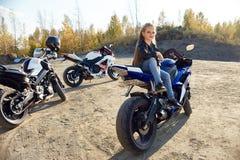 Menina nova que senta-se em uma competência da motocicleta, bonita pouco motociclista em uma bicicleta dos esportes na natureza A fotografia de stock
