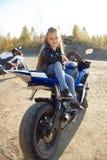 Menina nova que senta-se em uma competência da motocicleta, bonita pouco motociclista em uma bicicleta dos esportes na natureza A imagens de stock royalty free