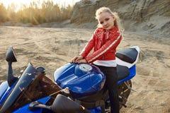 Menina nova que senta-se em uma competência da motocicleta, bonita pouco motociclista em uma bicicleta dos esportes na natureza A fotografia de stock royalty free