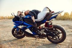 Menina nova que senta-se em uma competência da motocicleta, bonita pouco motociclista em uma bicicleta dos esportes na natureza A imagens de stock