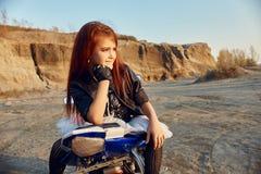 Menina nova que senta-se em uma competência da motocicleta, bonita pouco motociclista em uma bicicleta dos esportes na natureza A foto de stock