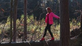 Menina nova, rural que anda em um log, contra a floresta do outono filme