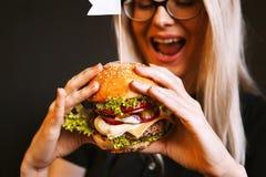 A menina nova, saudável bonita guarda um hamburguer grande saboroso com costoleta da carne Foto de Stock