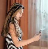 A menina o adolescente com o telefone celular perto de uma janela foto de stock
