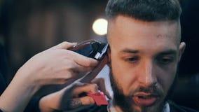 A menina o cabeleireiro corta a cabeça do ` s do indivíduo por uma tosquiadeira vídeos de arquivo