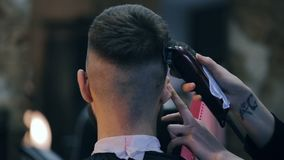 A menina o cabeleireiro corta o indivíduo com uma tosquiadeira filme