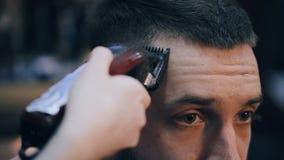A menina o cabeleireiro corta o indivíduo com uma tosquiadeira video estoque
