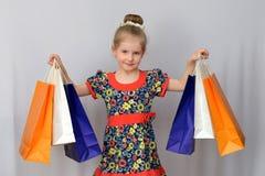 A menina, o comprador guarda os sacos de compras coloridos Imagem de Stock