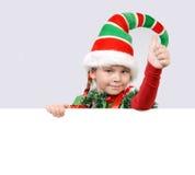 Menina - o duende de Santa que mostra a APROVAÇÃO do sinal com a bandeira Fotografia de Stock