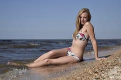 A menina o louro em um biquini que senta-se na praia na areia Jovem mulher bonita em um biquini colorido no fundo do mar Foto de Stock Royalty Free