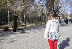 A menina observa um juggler com mostras das bolas de cristal Imagem de Stock