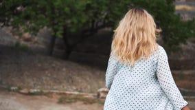 Menina obstinada com os passos de fluxo de cabelo louro da luz para a frente para encontrar o destino, senhora na blusa branca do video estoque