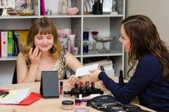 A menina obtém a fundação para o maquilhador das consultas Fotos de Stock
