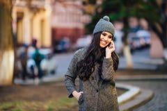Menina ocasional bonita nova que chama seu telefone celular na rua da cidade da mola Fotos de Stock