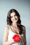 Menina ocasional de sorriso dos jovens com flor vermelha Imagem de Stock