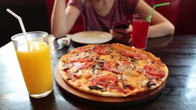 Menina ocasional que usa o smartphone em um café Suco e pizza frescos no primeiro plano video estoque