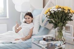 Menina ocupada positiva que manuseia acima ao encontrar-se na cama de hospital fotografia de stock
