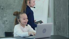 Menina ocupada que trabalha no escritório, usando o portátil e os fones de ouvido video estoque