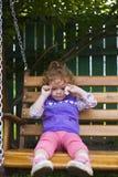 Menina ofendida que senta-se em um banco com cookies fotografia de stock