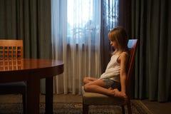 Menina ofendida que senta-se em uma cadeira imagens de stock